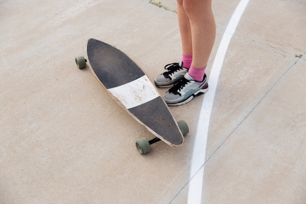 Cropped image of young female legs and skateboard outdoors over white