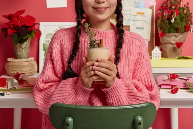 Cropped image of young girl wears oversized knitted sweater, holds eggnog in hands filled with cinammon, decorated by spruce, sits at chair against desktop, prepares for christmas celebration