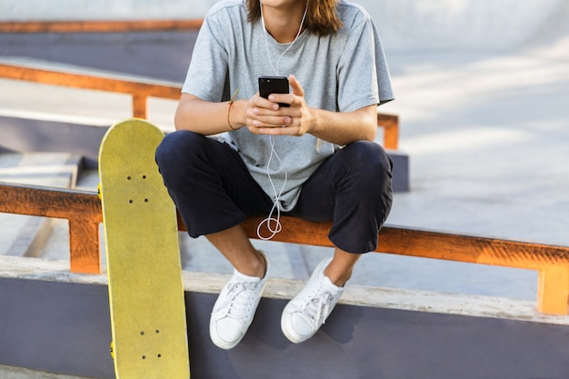 Cropped image of a young guy spending time at the skate park, listening to music with earphones