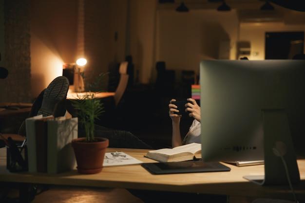 L'immagine ritagliata del designer giovane donna gioca per telefono.