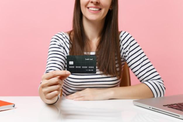 L'immagine ritagliata di una giovane donna sorridente in abiti casual con in mano una carta di credito si siede alla scrivania bianca