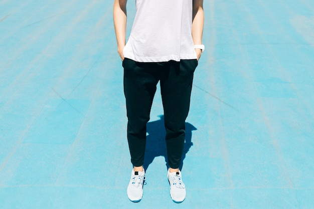 Cropped image of a young woman in a sports pants, t-shirt and sneakers standing on a blue sports grounds