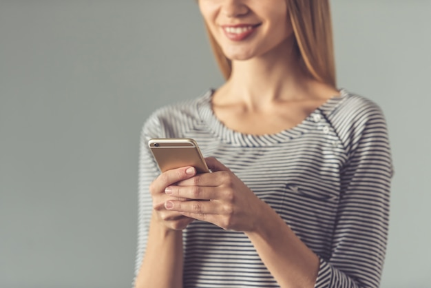 Cropped image of young woman using a smartphone