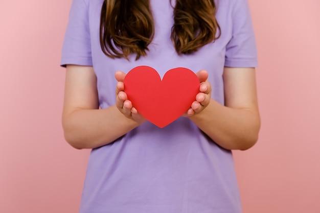젊은 여성 블로거의 자른 이미지는 분홍색 스튜디오 배경 위에 격리된 작은 붉은 마음을 손에 들고 있습니다. 블로그 블로그 소셜 네트워크 부드러움 개념처럼. 발렌타인 데이 국제 여성