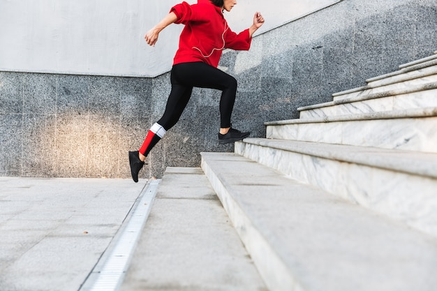 Cropped imge of a young sportswoman running up the stairs outdoors