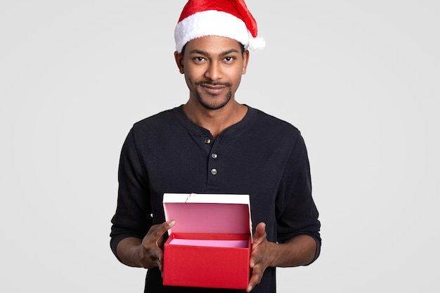 Cropped isolated dark skinned young male wears santa claus hat, carries opened red gift box, suggests you to buy present for christmas, stands on white. holiday concept