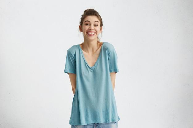 Обрезанный снимок харизматичной и позитивной женщины с легкой веселой улыбкой, держащей руки за спиной и наслаждающейся досугом в помещении