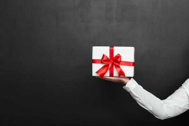 Mano maschio potata che tiene scatola attuale bianca con l'arco rosso, isolato sopra la parete grigio scuro