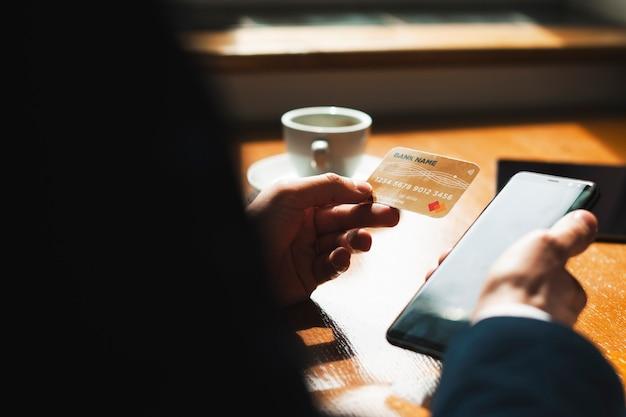 아름 다운 빛에 대 한 커피 숍에서 책상에 앉아 골드 신용 카드와 스마트 폰을 들고 남성 손을 잘립니다.