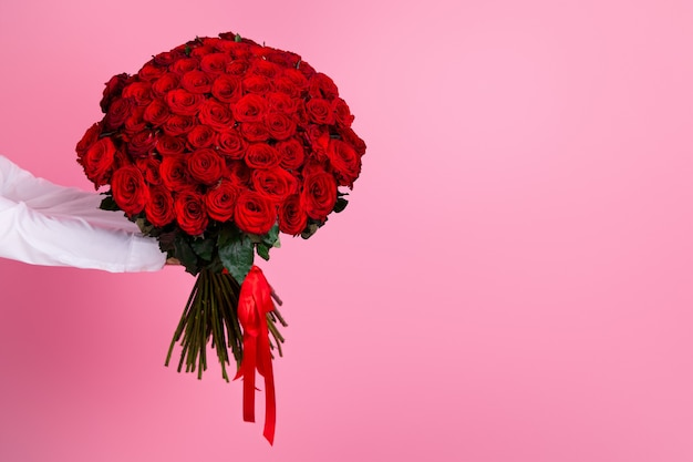 Of cropped man arms hold big one hundred red bright roses bunch