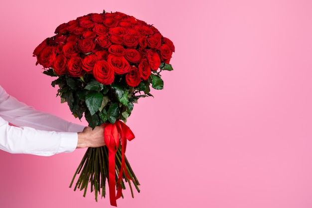 Cropped man arms hold big one hundred red bright roses