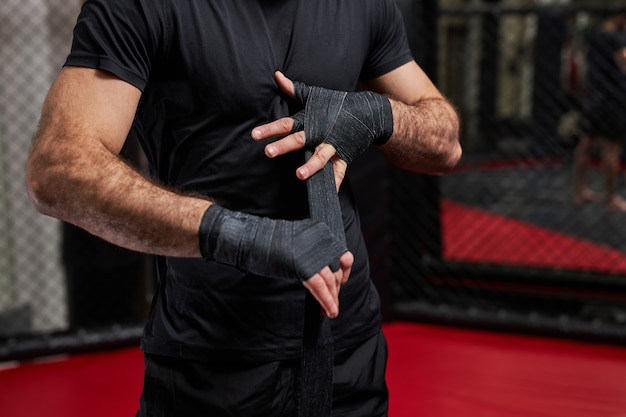 Cropped man in black sportswear preparing for tough fight, wrapping fist in sport protective bandages. standing on ring getting ready for mma fight