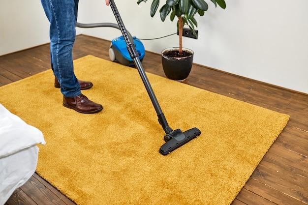 Обрезанный мужчина в повседневной одежде пылесосит желтый ковер, убирая белую современную гостиную. дом, концепция домашнего хозяйства. вид сбоку