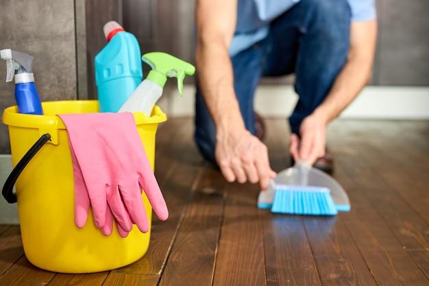 Обрезанный мужчина подметает пыль метлой на совке уборки концепции крупным планом фото