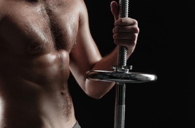 バーベルで裸の運動選手をトリミングしました。孤立した暗い背景