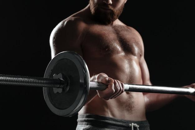 Обрезанный голый мускулистый мужчина со штангой. изолированный темный фон