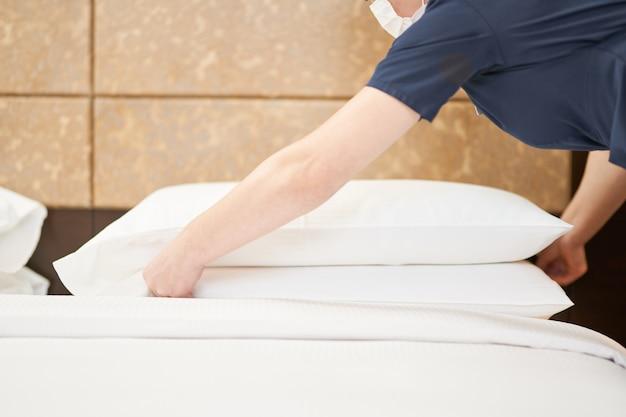 Обрезанная горничная в маске поправляет белые подушки на кровати в гостиничном номере. концепция гостиничного обслуживания
