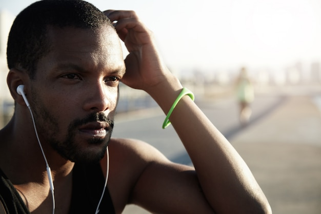 Cropped outdoor portrait of black sportsman sitting on pavement in deep thoughts, touching his head, looking tired after intensive training outside, listening to motivating audiobook in his earphones