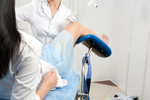 산부인과 의자에 앉아있는 환자를 검사하는 산부인과 의사의 자른 파노라마. 여성 건강 개념.