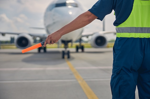 Cropped photo of an airport worker in uniform holding a marshaling wand in one hand