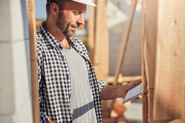 Cropped photo of a calm man in a hard hat looking at a clipboard with a plan of a building