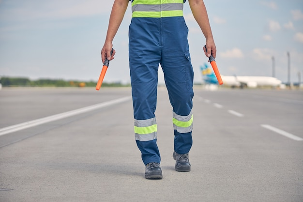Cropped photo of a caucasian male in safety overalls holding a pair of marshaling wands