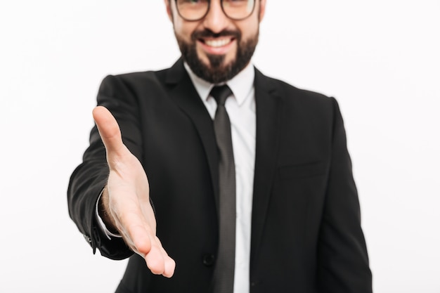Cropped photo of cheerful businessman in suit and eyeglasses shaking hand while attending meeting or job interview, isolated over white wall