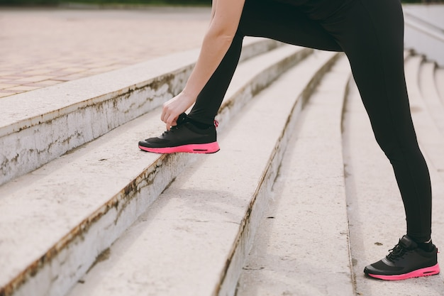 Cropped photo close up of female hands tying shoelaces on woman black and pink sneakers on training on stairs outdoors