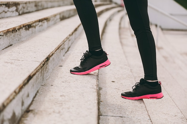 Cropped photo close up of female legs in sportswear, black and pink woman sneakers doing sport exercises, climbing on stairs outdoors