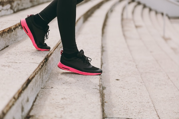 Cropped photo close up of female legs in sportswear, black and pink woman sneakers doing sport exercises, going down on stairs outdoors