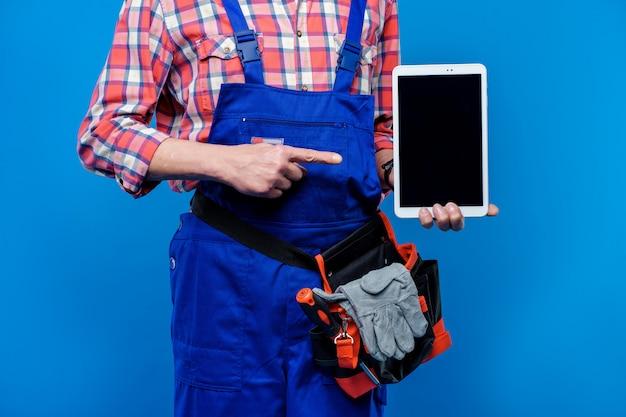 Обрезанное фото, строитель и сантехник с белым ноутбуком, изолированных на синем