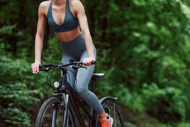 Foto ritagliata. ciclista femminile su una bici su strada asfaltata nella foresta durante il giorno