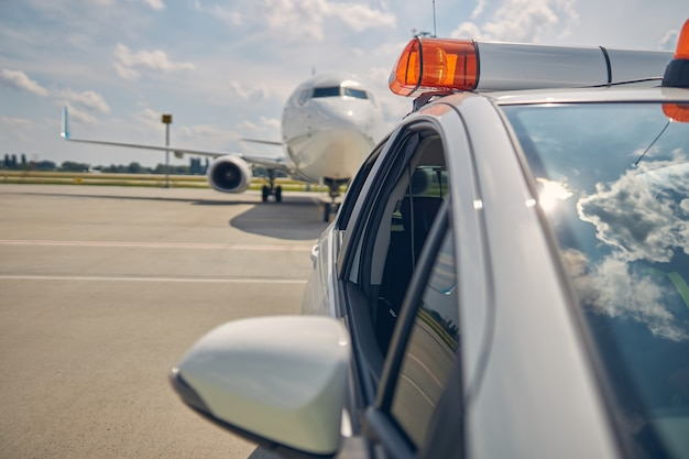 Cropped photo of a follow-me car directing the newly arrived airplane to the parking spot