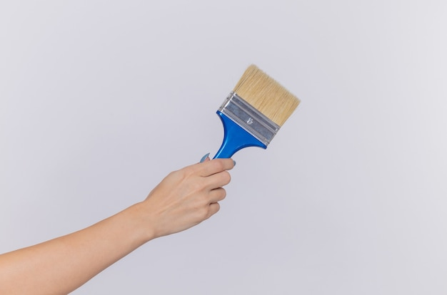 Cropped photo of hand of woman holding paint brush over isolated white wall
