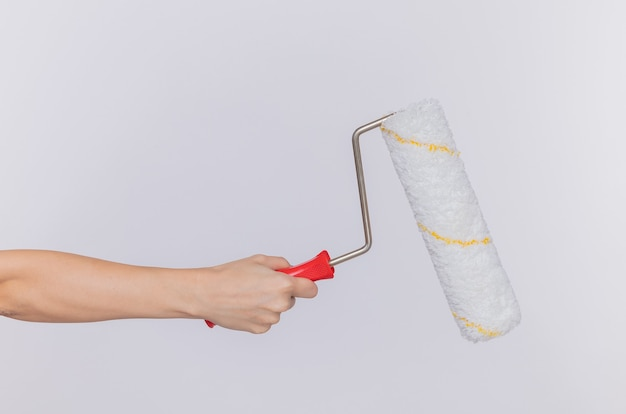 Cropped photo of hand of woman holding paint roller over isolated white wall