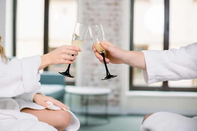 Cropped photo of hands of two people in white bathrobes holding glasses of shampagne and toasting. man and woman hands with full champagne glasses