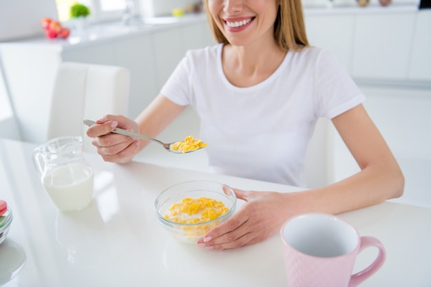 Cropped photo of housewife hands holding spoon pouring fresh milk cooking breakfast cornflakes tasty healthy eating concept sitting table white light kitchen indoors