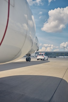 Cropped photo of a landed large civil aircraft following the ground vehicle at the airport