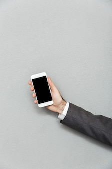 Cropped photo of male hand holding smartphone with blank screen isolated over gray, copy space