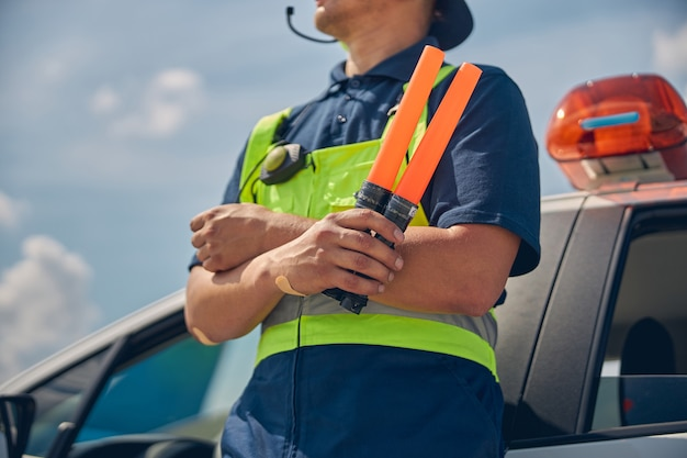 Cropped photo of a male worker in the safety overalls leaning his back against the car