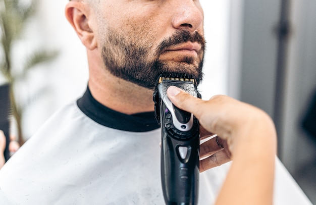 Cropped photo of a man being shaved by a hairdresser with an electric razor in a salon
