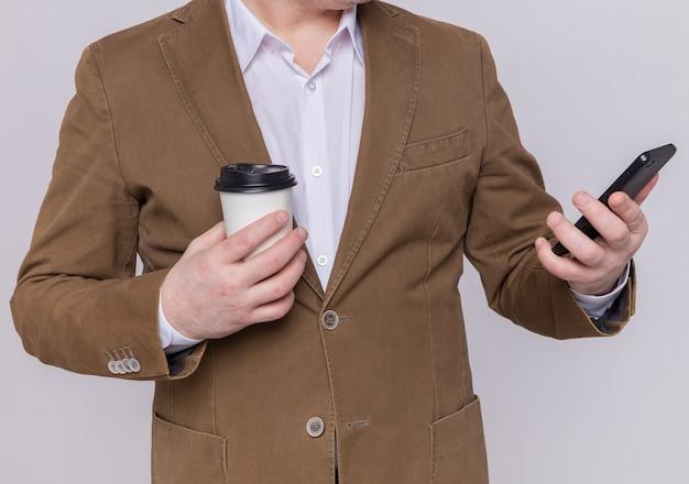 Foto ritagliata dell'uomo in vestito che tiene il telefono cellulare e il bicchiere di carta in piedi sopra il muro bianco