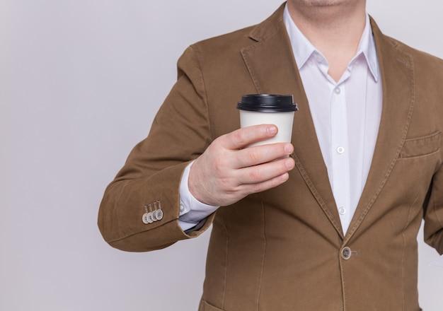 Foto ritagliata dell'uomo in vestito che tiene il bicchiere di carta in piedi sopra il muro bianco