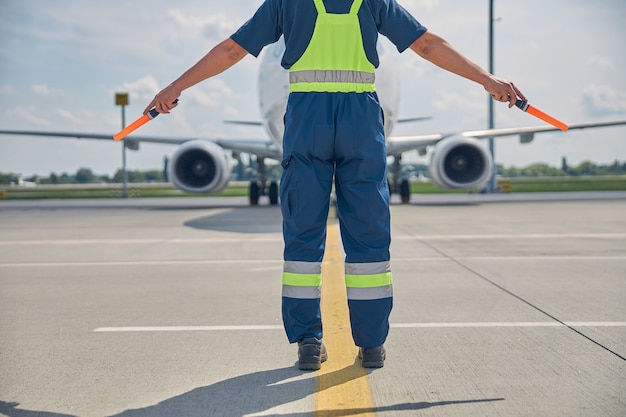 Cropped photo of a marshaller making the hold signal to the pilot in the airplane