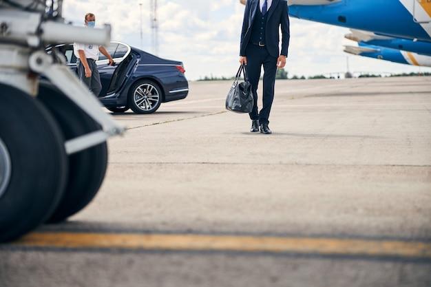 飛行機を通り過ぎて歩いているダッフルバッグを運ぶビジネスマンのトリミングされた写真