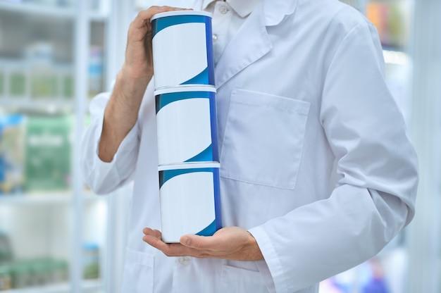 新しい栄養補助食品を手にした3つの瓶を持っている白人薬剤師のトリミングされた写真