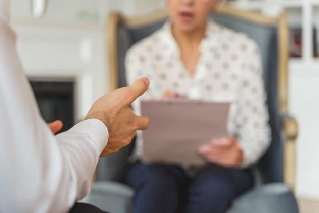 클라이언트 앞 안락의자에 앉아 있는 여성 심리학자의 자른 사진
