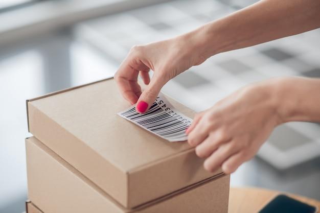 사무실 책상에 있는 판지 상자에 바코드를 붙인 여성 근로자의 자른 사진