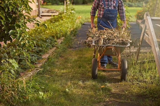 정원 경로를 따라 마른 잡초로 가득 찬 카트를 밀고 있는 정원사의 자른 사진