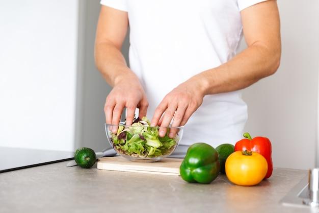 家庭の台所で野菜を調理しているハンサムな若い男のトリミングされた写真はサラダを作ります。